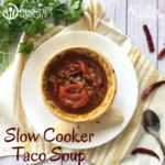 Slow cooker Taco Soup recipe ready to warm you up! plated in a bowl surrounded by chilis and cilantro.