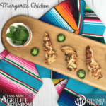 Margarita Chicken breast recipe on cutting board with side of sliced jalapenos, splayed over a colorful serape cloth